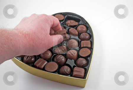 Valentines Candy stock photo, Reaching in to a box of chocolate Valentine candy. by Robert Byron