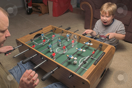 Foosball Players stock photo, A man and a boy playing a game of foosball. by Robert Byron
