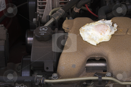 Frying an Egg on a Car Motor stock photo, Cooking an egg on an automobile engine. by Robert Byron