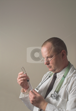 Doctor with a Syringe stock photo, A medical doctor preparing an injection in a syringe. by Robert Byron