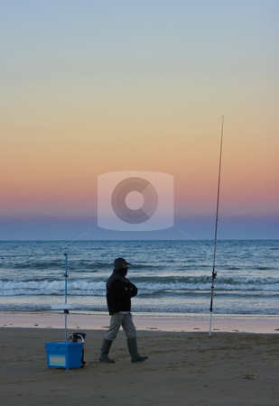 Fisherman standing on beach stock photo, Image of an angler and his tackle fishing from the beach by Ivan Montero