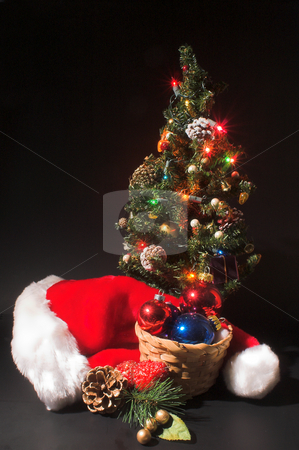 Christmas Scene stock photo, Christmas Scene - Santa hat, a Christmas tree and a basket of ornaments. by Robert Byron