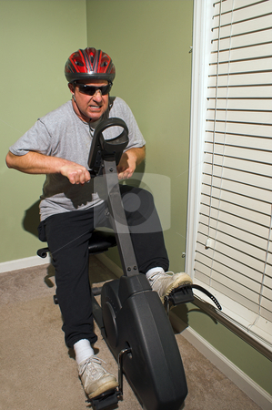 Exercise Biker stock photo, A safety conscious man on an exercise bike. by Robert Byron