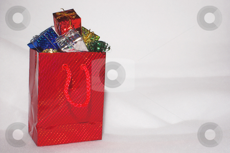 Christmas Presents in the Snow stock photo, Christmas presents in a festive shopping bag in the snow. by Robert Byron