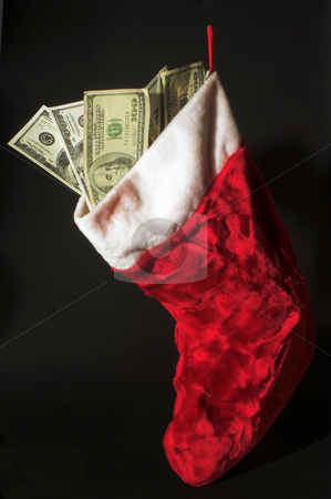 Christmas Money stock photo, A red Christmas stocking loaded with cash. by Robert Byron