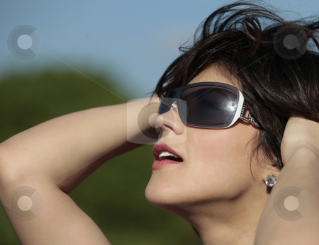 Woman in sunglasses stock photo, Profile view of a beautiful young lady with dark sun glasses outdoor looking at the sun smiling by Claudia Veja