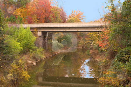 Fall Colors Bridge stock photo, A bridge spanning across a creek in the autumn. by Robert Byron