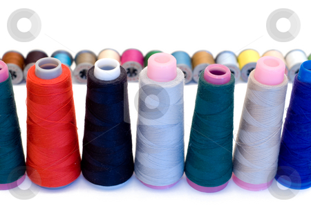 Sew stock photo, Spools of sewing thread lined up in rows, isolated on a white background by Richard Nelson