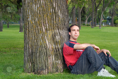Relaxing stock photo, A young man relaxing and leaning against a tree in the park by Richard Nelson