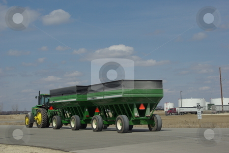 Tractor towing grain wagons stock photo, A John Deere tractor tows two big grain wagons into the Fairbank, Iowa biofues plant. Iowa leads the nation in the number of  biofuel production facilities making ethanol from corn with 25 now in operation.  Seventeen more plants are under construction or planning stages (photo 04/02/2008). by Dennis Thomsen