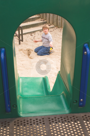 Boy Playing at a Playground stock photo, A little boy digging in the sand at a playground. by Robert Byron