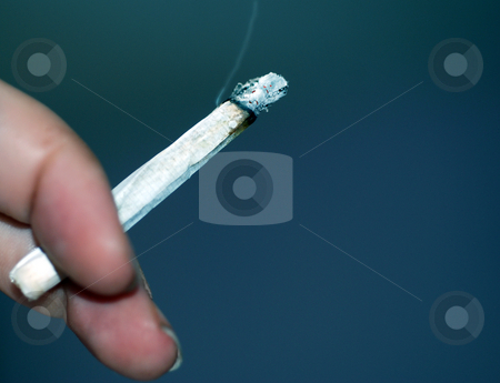 Smoking A Roll-Up stock photo, A close up photograph of someone's hand who is smoking a rolled cigarette by Philippa Willitts