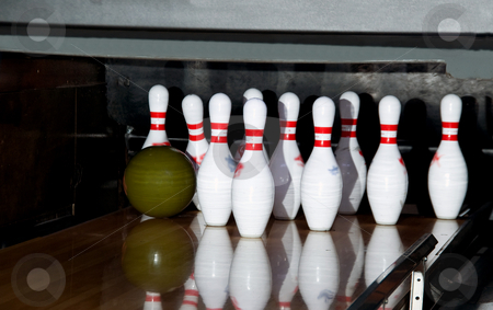 Bowling stock photo, A ball striking a set of pins on a bowling alley. by Robert Byron