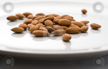 Shelled Almonds on White stock photo, Group of almonds on shiny white plate by Mark S