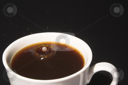 Milk Splash in Coffee stock photo, Drop of milk splashing into a cup of coffee. by Robert Byron