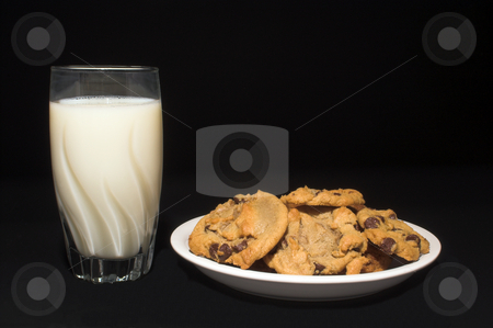 Milk and Chocolate Chip Cookies stock photo, A plate full of chocolate chip cookies and a glass of milk. by Robert Byron