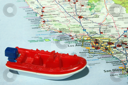 Boating stock photo, A toy boat on a road atlas. by Robert Byron