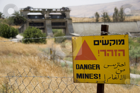 Danger, Mines sign stock photo, Danger, Mines! sign in english, arabic, and hebrew hanging on barbed wire fence with dam flood gates in background. Peace Island, Bakoura, Jordan. by Andrei Harwell