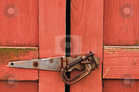 Barn Door stock photo, A red barn door with a c-clamp lock. by Robert Byron