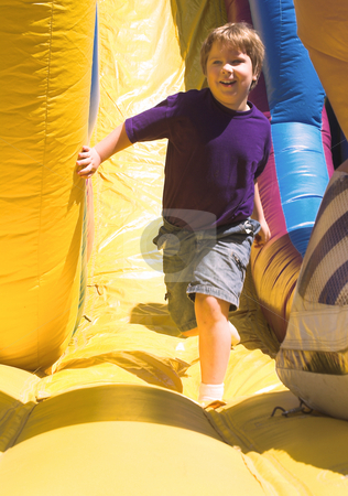 Boy at Carnival stock photo, A young boy playing on a carnival obstical course. by Robert Byron
