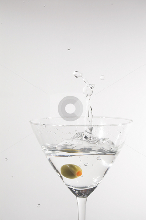 Martini stock photo, A dry martini with a green olive. by Robert Byron