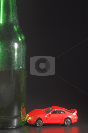Half full beer with model car stock photo, A drunk driver crashes his car into a giant beer bottle. DUI / DWI Concept by Robert Byron