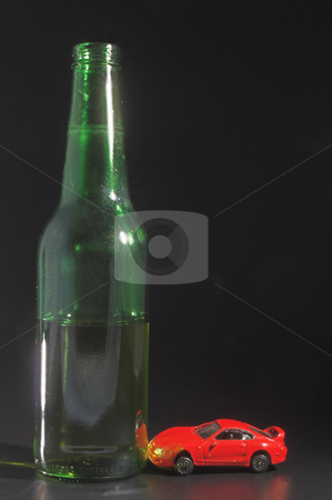 Half full beer with car stock photo, A drunk driver crashes his car into a giant beer bottle. by Robert Byron