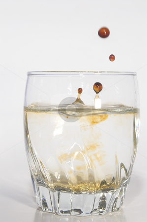 Tainted Water stock photo, Oil drops polluting clean water in a drinking glass. by Robert Byron