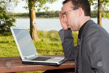 Businessman stock photo, A young businessman working on his laptop outside by Richard Nelson