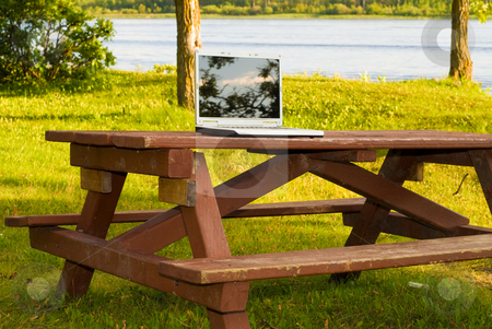 Laptop In The Park stock photo, A laptop computer resting on a picnic table outside in a park by Richard Nelson