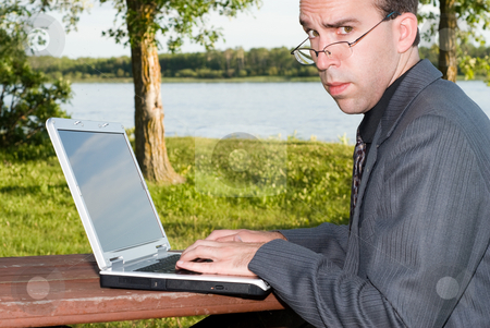 Serious Employee stock photo, A serious employee working on his laptop outside in a park by Richard Nelson