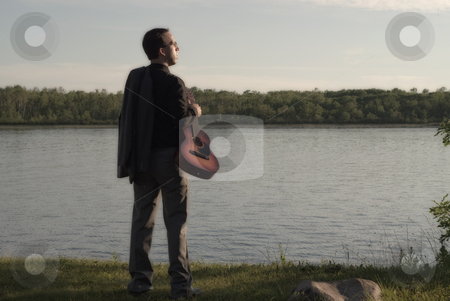 Music Man stock photo, A man standing by a small lake with a guitar, done in dark colors by Richard Nelson