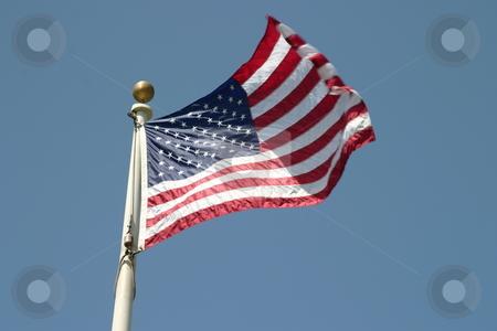 USA Flag stock photo, Waving USA american flag on blue sky background. by Henrik Lehnerer