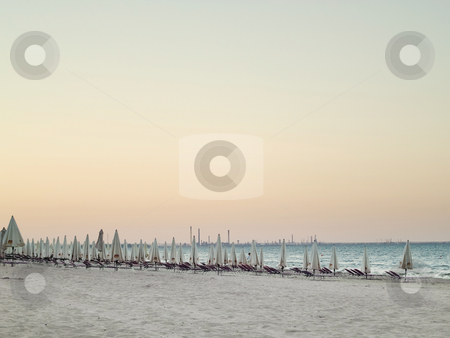 Lounge chairs stock photo, Rows of lounge chairs and umbrellas on the beach by Adrian Costea