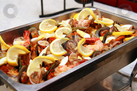 Seafood paella stock photo, Seafood paella served with lots of lemon toppings by Jonas Marcos San Luis