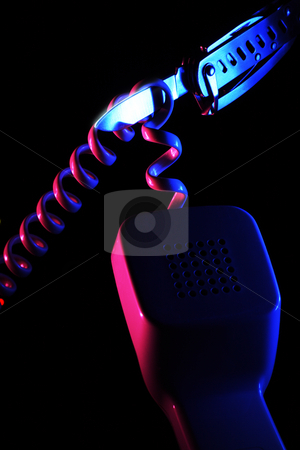 Knife and wired telephone handset stock photo, Attempt to cut spiral shaped wire of the telephone handset by swiss knife illuminated by blue and pink colored light sources on the black background by Andrey Yanevich