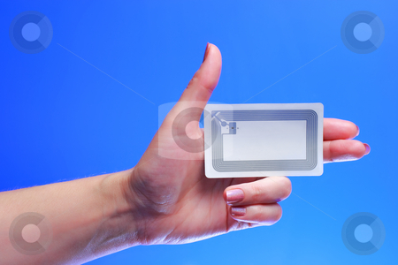 Hand with EPC RFID tag stock photo, A studio shot of a woman holding in her hand Radio-frequency identification (RFID) tag card. Room for text, or your own message. There is a transponder with antenna and embedded integrated electronic circuit on chip for receiving and transmitting signal with Electronic Product Code (EPC). by Andrey Yanevich