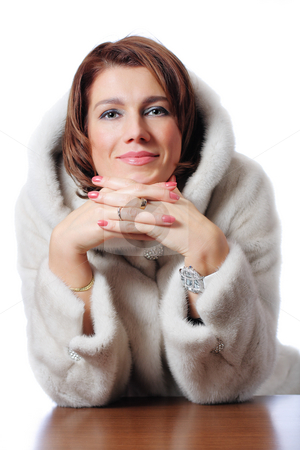 Young beautiful women in the fur sitting at the table stock photo, A studio shot of a young beautiful women in the fur sitting at the table (Snow Maiden) by Andrey Yanevich