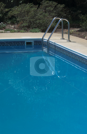 Pool Ladder stock photo, A ladder leading in to a pool of deep blue water. by Robert Byron