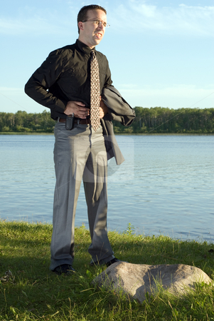 Stomach Pains stock photo, A young businessman holding his stomach at the lake, because he has a stomach ache by Richard Nelson