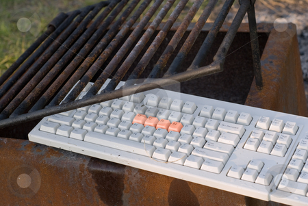 Burn Technology stock photo, A computer keyboard in a fire pit with the word burn on it by Richard Nelson