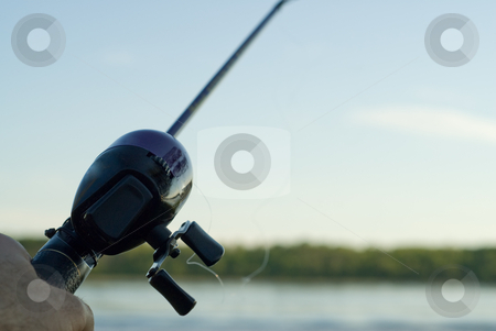 Fishing rod stock photo, Someone fishing with a fishing rod and reel in a lake by Richard Nelson