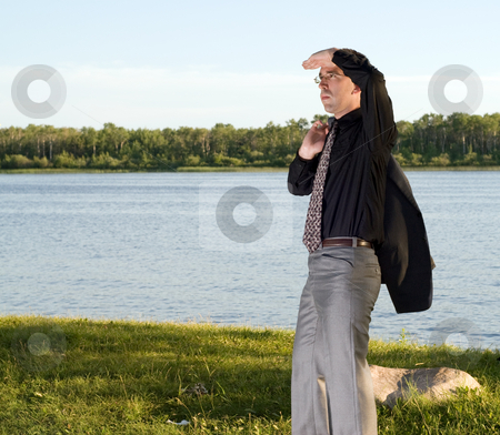 Lookout stock photo, A young businessman standing by a small lake, holding his hand over his eyes to see better by Richard Nelson