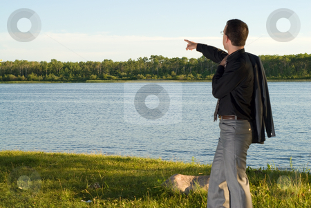 Businessman At The Lake stock photo, A young businessman out of focus, pointing at something over the lake by Richard Nelson