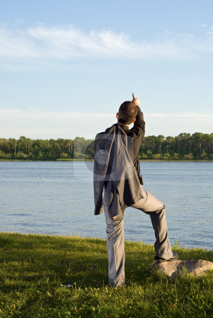 Sight Seeing stock photo, A young man wearing a grey suit pointing at something in the sky by Richard Nelson