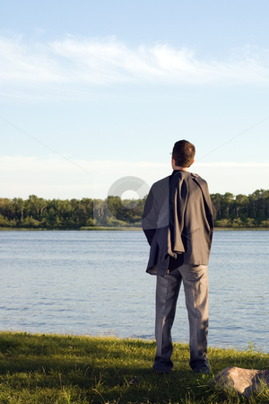 Businessman at Peace stock photo, A businessman relaxing by a small lake after work by Richard Nelson