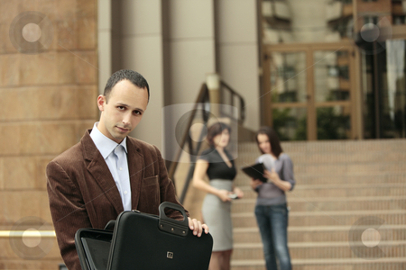 The deal is ready to be signed  stock photo, Business man looking at the camera with his briefcase opened and business ladies talking in the background in front of a building by Claudia Veja