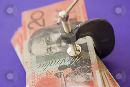 Reduced spending stock photo, A wad of australian 20 dollar notes pressed in a G clamp by Stephen Gibson