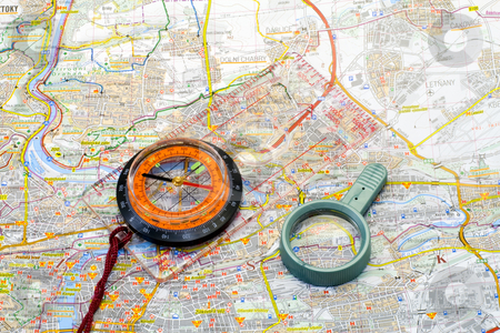 Compass and handglass on a map stock photo, A compass and a handglass lying on a map - close up by Petr Koudelka