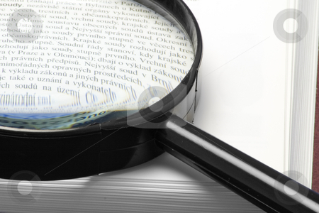 Hand-glass on a book stock photo, Magnifying glass on a book - close-up by Petr Koudelka
